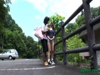 एशियाई लड़की गड़बड़ जबकि बाड़ आउटडोर के लिए झुकने