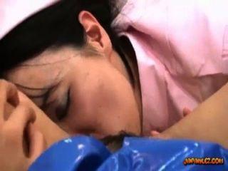पुलिस की वर्दी में एशियाई लड़की एक नर्स द्वारा खिलौना के साथ गड़बड़ पाला बिस्तर पर