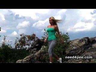 स्पोर्टी गोरा चट्टानों पर एक पेशाब के लिए नीचे हो जाता है