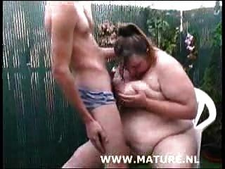 मोटी कुतिया बगीचे में मुर्गा चूसने और क्रीमयुक्त उसके स्तन हो रही