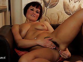 सोफे पर गर्म बालों वाली गर्म महिला हस्तमैथुन