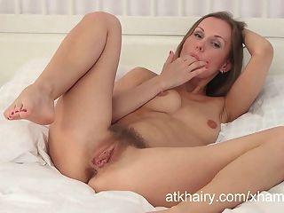Lera एक सफेद बिस्तर पर masturbates