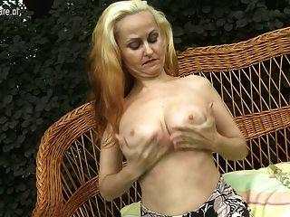 बगीचे में उसे गीला बिल्ली के साथ खेल गर्म गोरा माँ