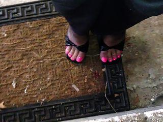 गुलाबी toenails और खच्चरों के साथ काले मोज़ा