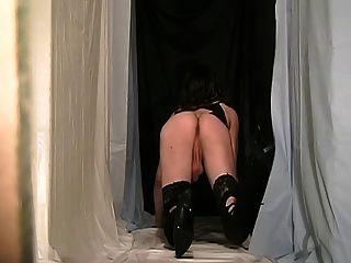 पिछाड़ी सीडी एक विशेष काली पोशाक पहने हुए crossdresser