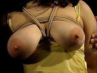 पीले रंग की पोशाक में बड़े स्तन आकर्षक बाध्य और उसके स्तन कपड़े खूंटे के साथ कवर किया गया है