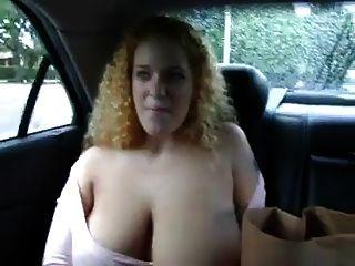 संचिका लाल बालों वाली एक कार के पीछे से उसके स्तन से पता चलता है