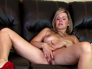 चमड़े के सोफे पर अद्भुत शौकिया परिपक्व माँ