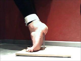 पैर यातना नाखून के साथ tiptoes पर खड़ा है और बंधे