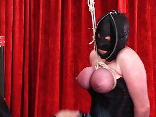 चमड़े के हुड में कोर्सेट मुड़ी हुई महिला को बाध्य किया जाता है ताकि वे लाल हो जाएं