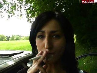 कार से एक चेहरे को पाने के बाद जर्मन लड़की धूम्रपान करती है