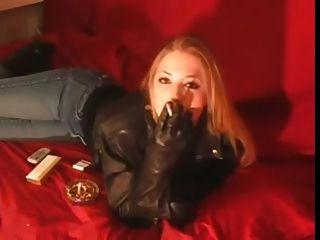 काले चमड़े की जैकेट और दस्ताने में 120 मिमी की लड़की धूम्रपान करें