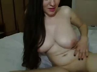 लंबे काले बाल लड़की, बिस्तर पर बड़े स्तन बिल्ली पथपाकर