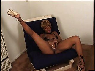 सेक्सी आबनूस ऊँची एड़ी के जूते में उसकी रसदार बिल्ली एक कुर्सी पर