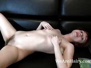 तिकड़ी स्ट्रिप्स और उसके काले सोफे पर masturbates