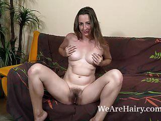ल्यूसिया साइबेरिया उसके भूरे रंग के सोफे पर नग्न स्ट्रिप्स