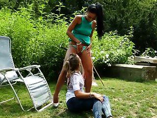 दो युवा लड़कियां बुत के रूप में बगीचे में पेशाब