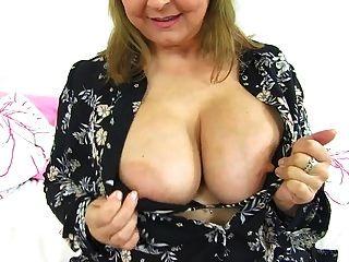 सुडौल ब्रिटिश परिपक्व माँ उसके बड़े स्तन के साथ खेल रही है और